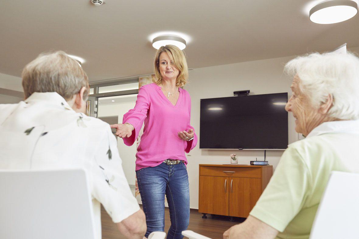Ilona Lamm motiviert eine Seniorin, als erste mit der MemoreBox zu spielen. Sie reicht ihr die Hand.
