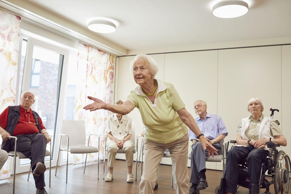 Eine Seniorin macht eine Handbewegung, als würde sie eine Kegelkugel werfen.