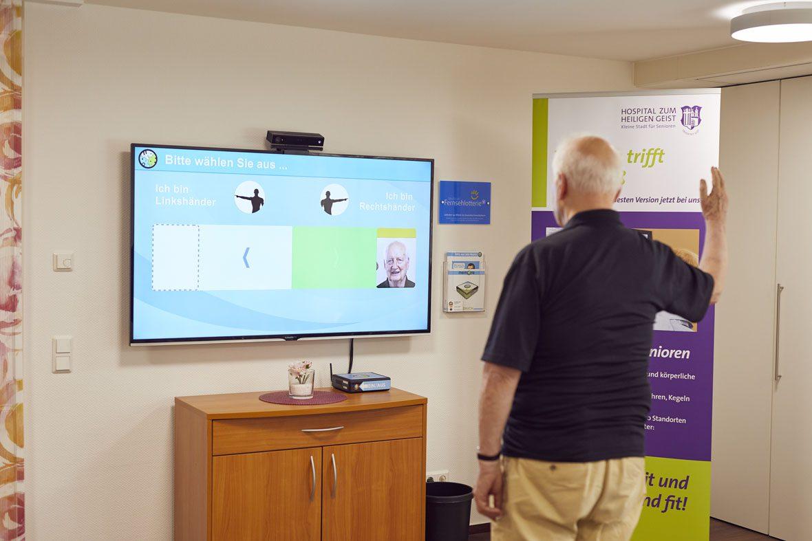 Ein Senior hebt den rechten Arm und steht vor dem Bildschirm auf dem das Computerspiel der MemoreBox angezeigt wird.