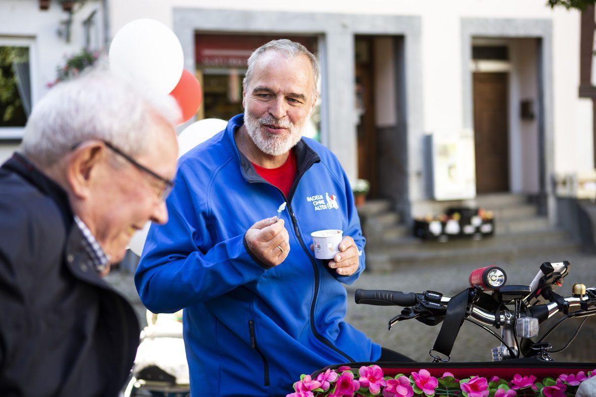 Der Ehrenamtliche Uwe Beu isst Eis aus dem Becher und unterhält sich mit einem älteren Herrn im Vordergrund.