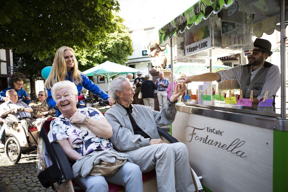 Eisverkäufer Mirko reicht dem ältern Herrn in der Rikscha einen Eisbecher über seinen Eistand hinweg. Die Sitznachbarin in der Rikscha lacht.