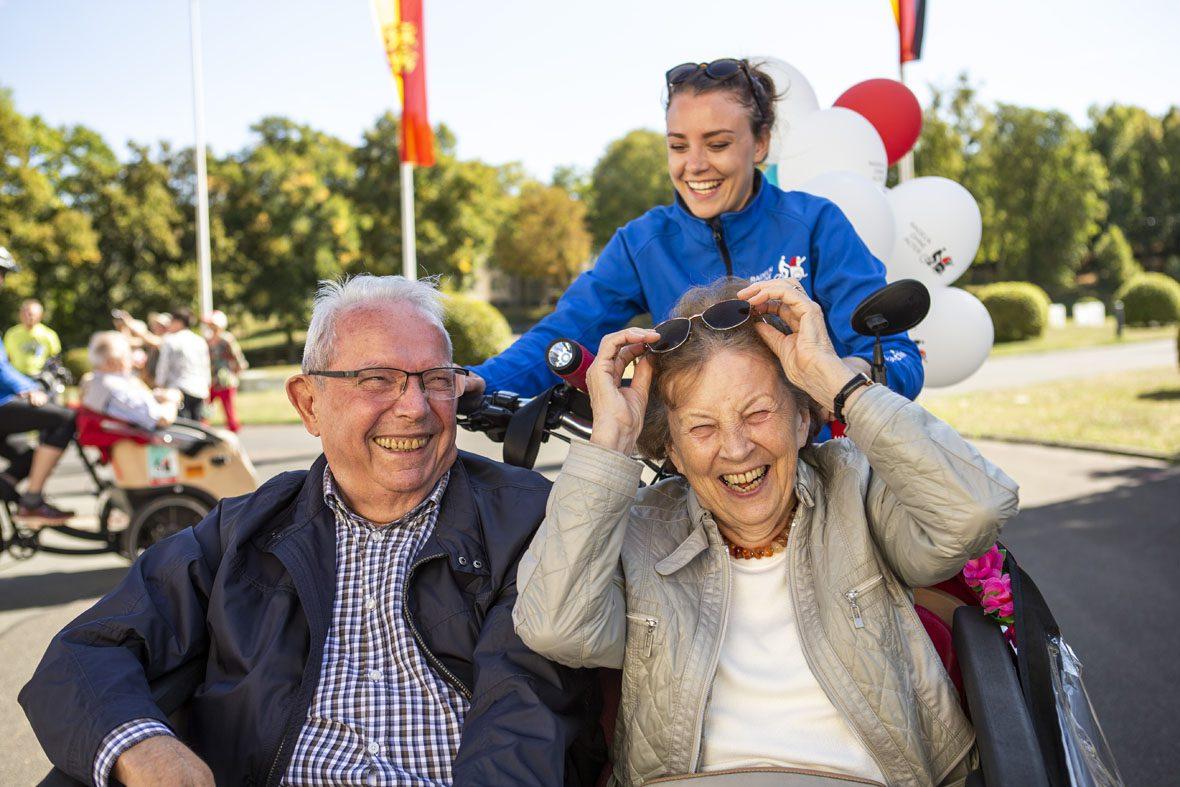 Der ältere Herr und die ältere Dame in der Rikscha lachen, die Dame greift nach ihrer Sonnenbrille.