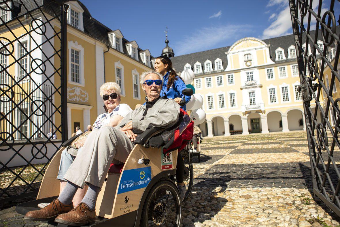 Die Rikschas fahren wieder vom Schlosshof herunter, auf der Seite der Rikscha sieht man das Logo der Deutschen Fernsehlotterie. Die Senioren tragen Sonnenbrillen, denn das Wetter ist sonnig.