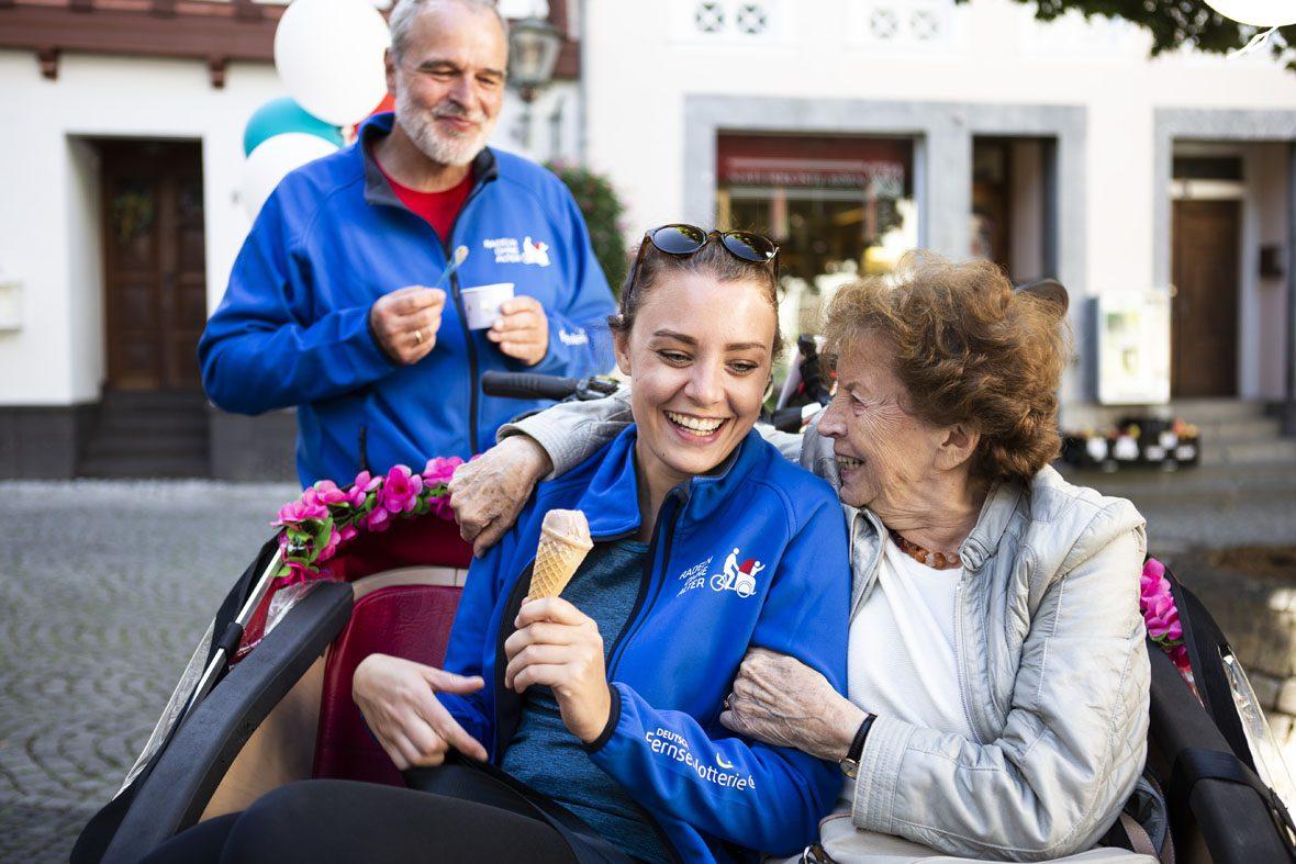 Caroline Kuhl sitzt mit einer Seniorin in der Rikscha, die Seniorin umarmt die Studentin und schaut sie lachend an.