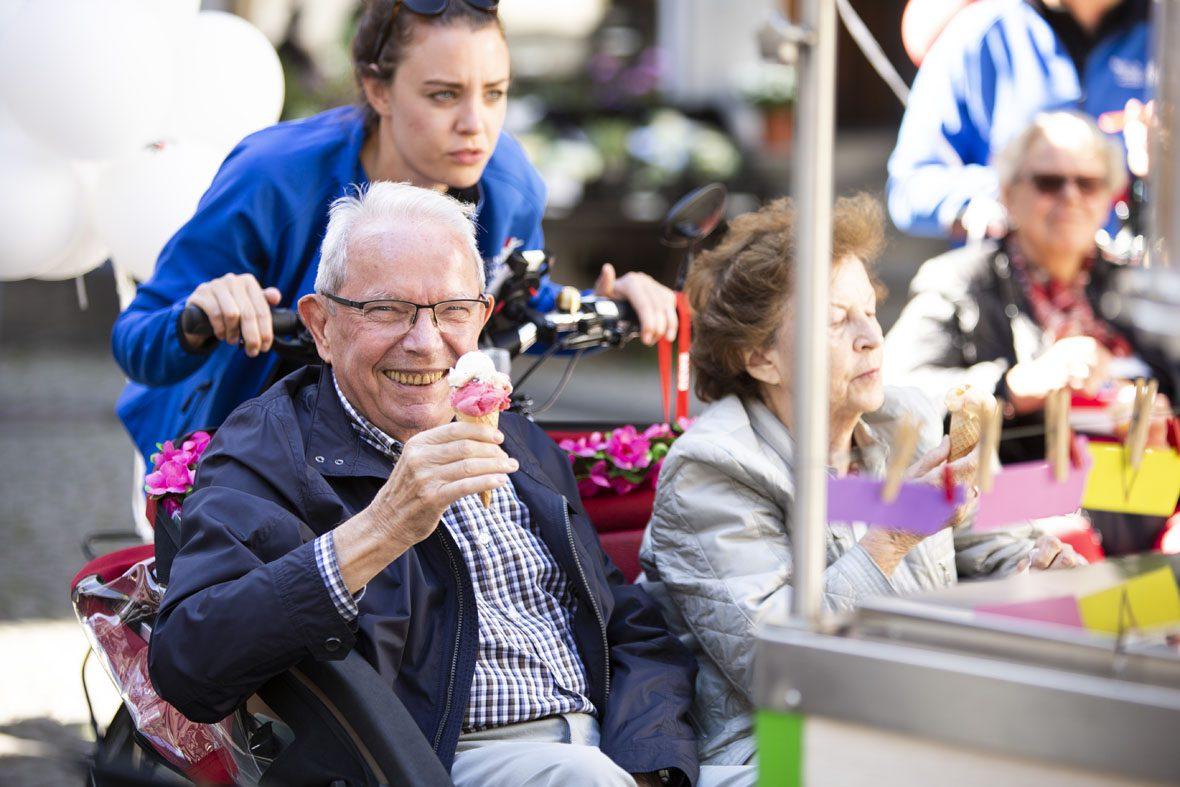 Ein älterer Herr sitzt in der Rikscha und hält ein Eishörnchen mit zwei Kugeln Eis darin in der Hand.