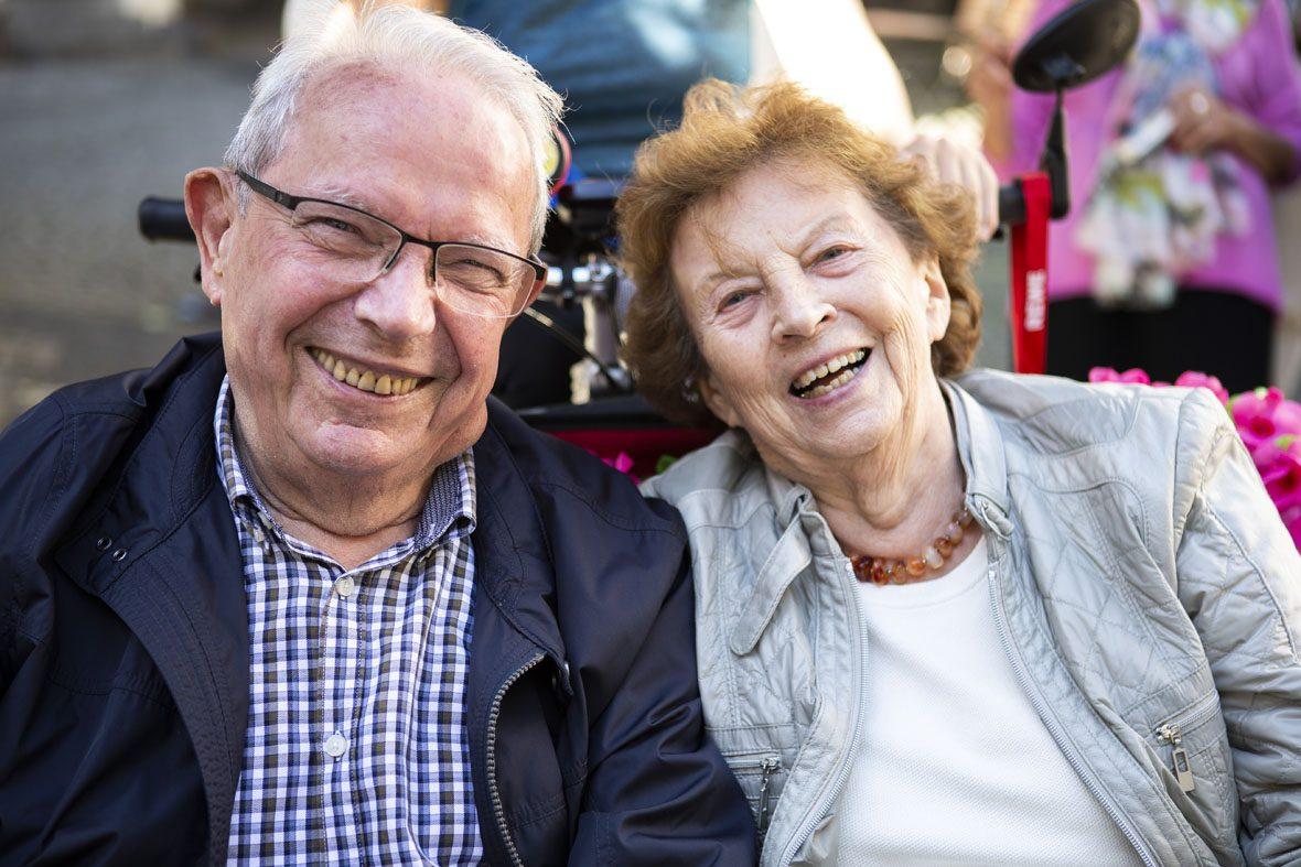Ein älterer Herr und eine ältere Dame schauen fröhlich in die Kamera. Sie sitzen nebeneinander in der Rikscha.