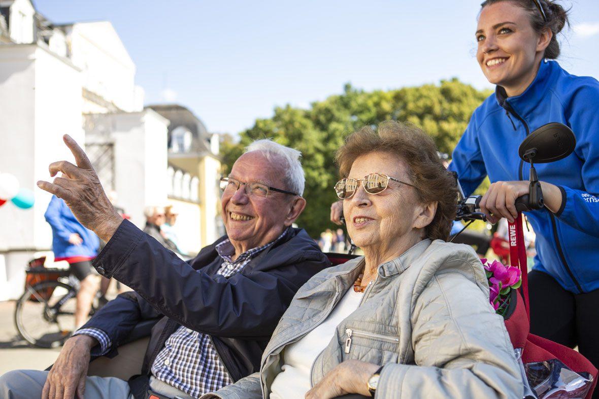 Ein älterer Herr in der Rikscha zeigt Fahrerin Caroline etwas in der Ferne, in der Sonnenbrille seiner Sitznachbarin spiegelt sich die Fassade des Schloss Oranienstein.