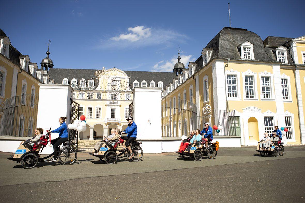 Vier Fahrradrikschas mit Faherer*innen und Passagieren fahren am Schloss Oranienstein in Diez entlang.