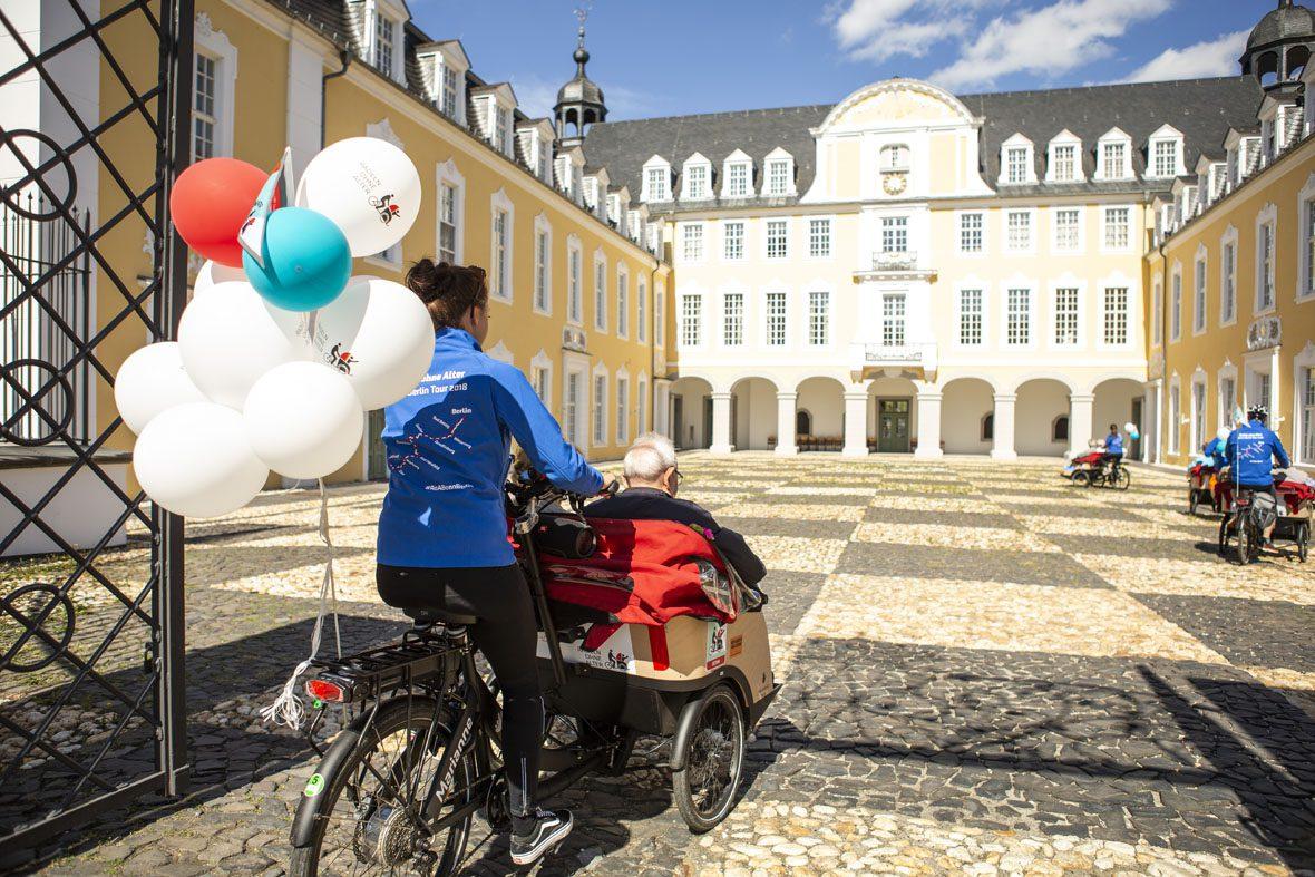 Vier Fahrradrikschas mit Faherer*innen und Passagieren fahren auf den Hof des Schloss Oranienstein in Diez .