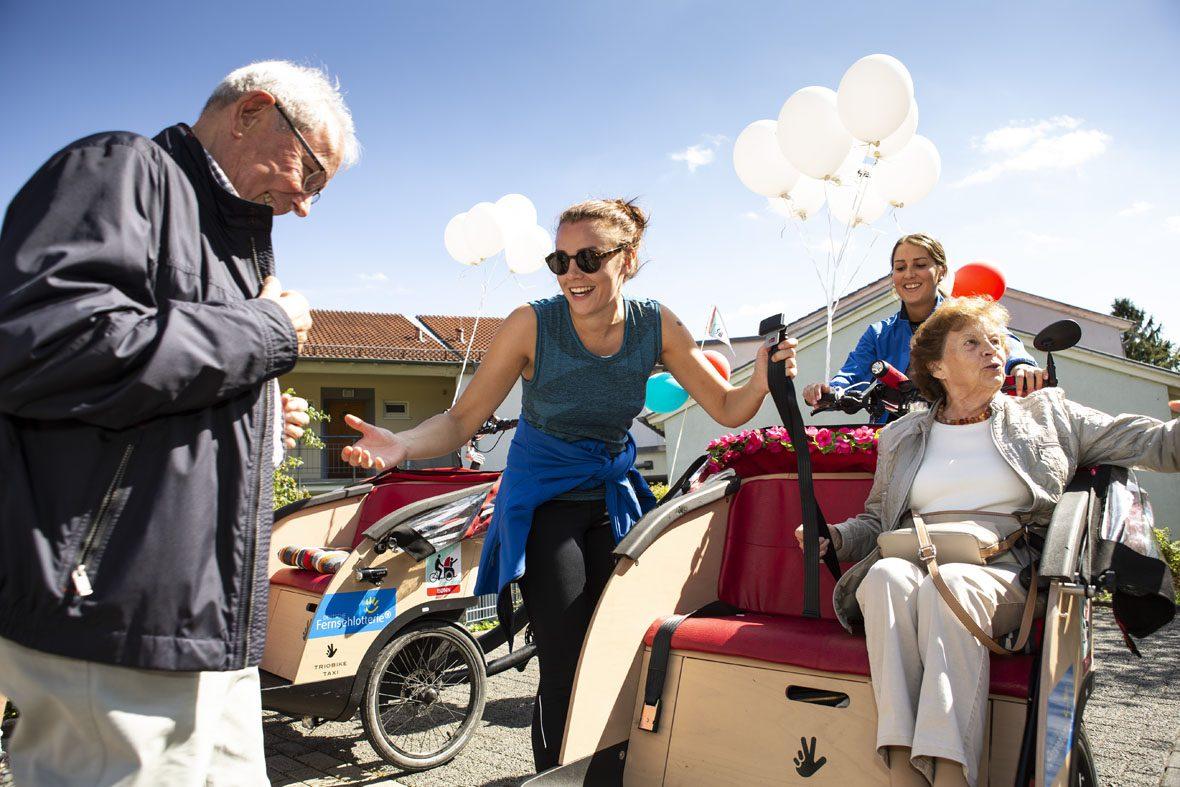 Caroline Kuhl hilft einem älteren Mann beim Einstieg in die Fahrradrikscha.