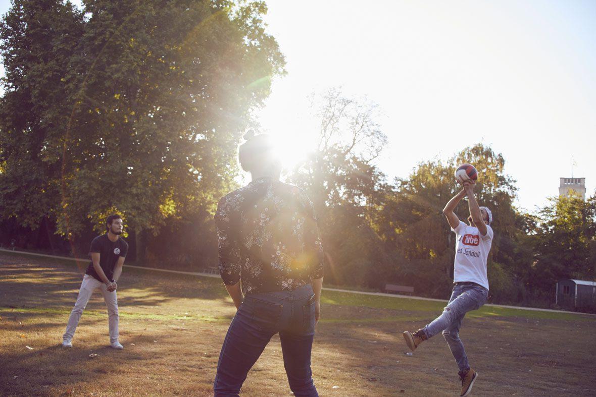 Ahmed pritscht den Volleyball zu Denise, im Hintergrund steht Eduardo.