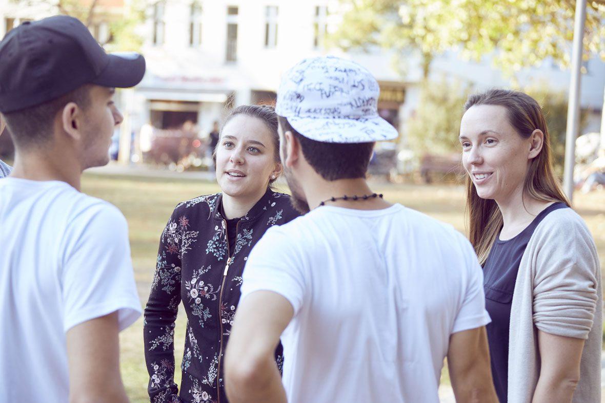 Tawfik und Ahmed stehen bei Denise und Natscha und unterhalten sich mit den beiden.