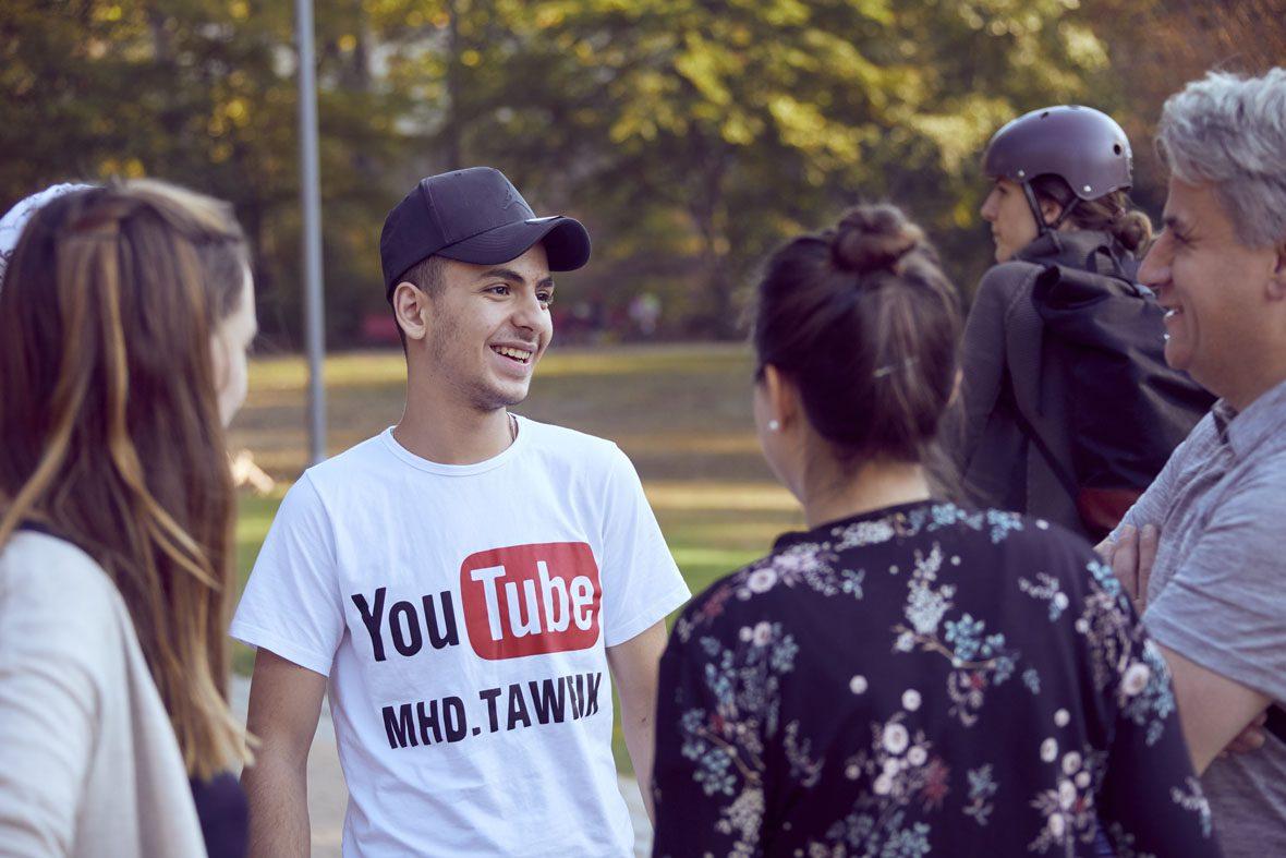 Tawfik trägt sein YouTube-Shirt und lächelt Amadeus an. Danaben stehen Denise und Natascha.