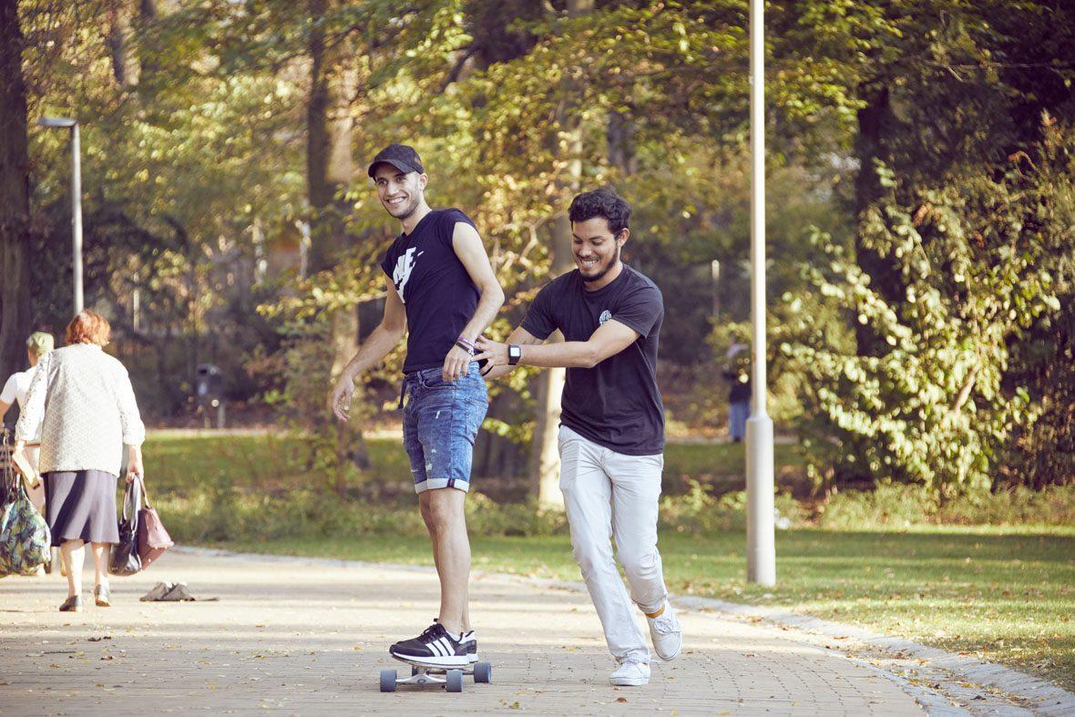 Salam versucht sich am Longboardfahren, Eduardo stützt ihn dabei und läuft neben dem Board her.