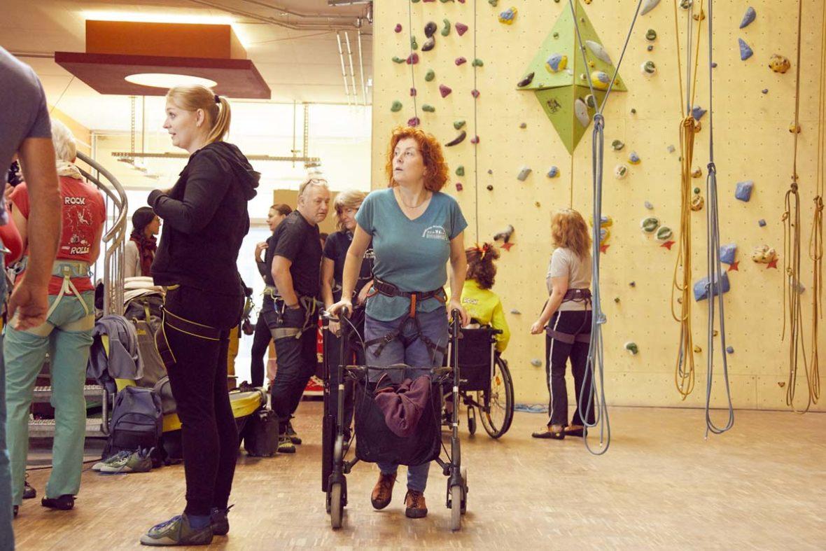 Sanna steht, auf ihren Rollator gestützt, in der Kletterhalle und blickt nach oben. Um sie herum stehen Menschen.