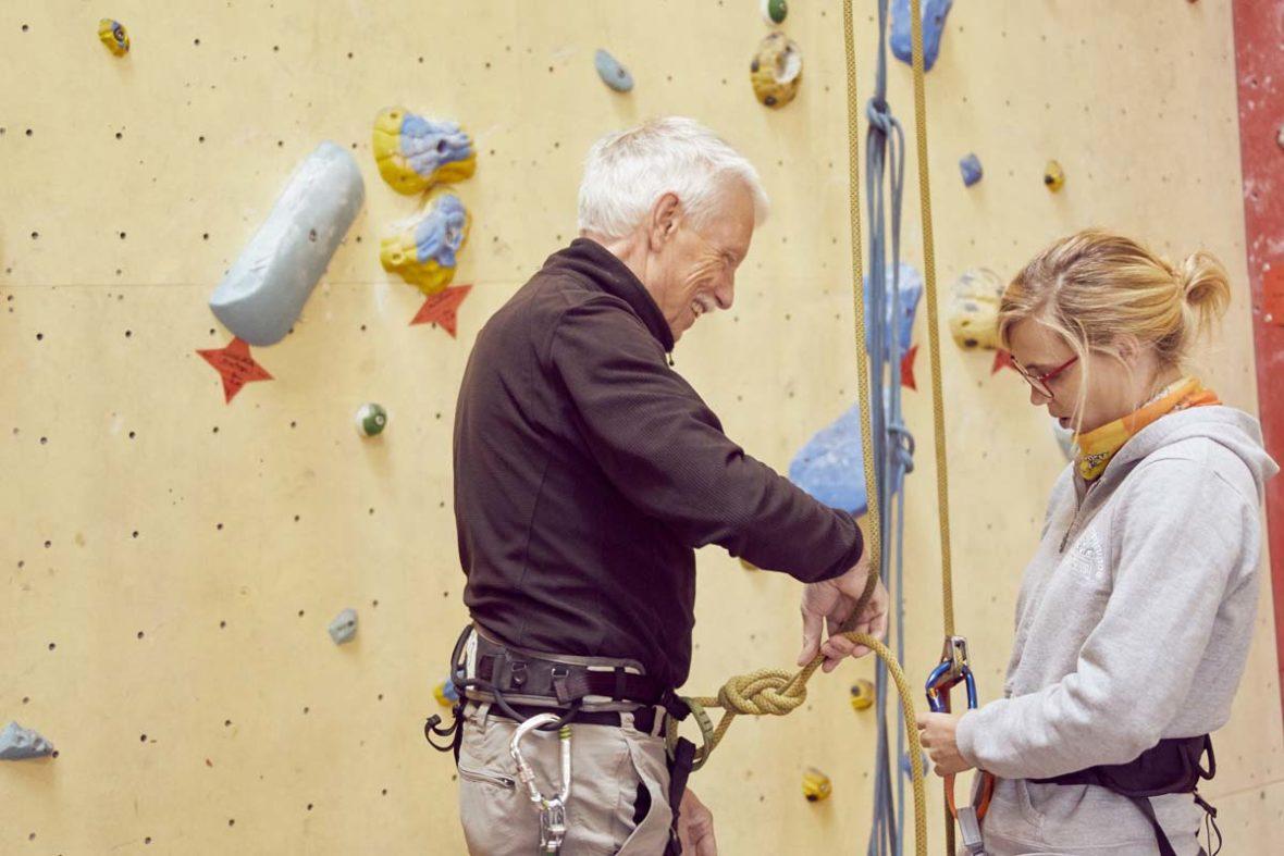Zwei Kletterer, ein älterer Herr und eine junge Frau, überprüfen Karabiner und Knoten in den Seilen.