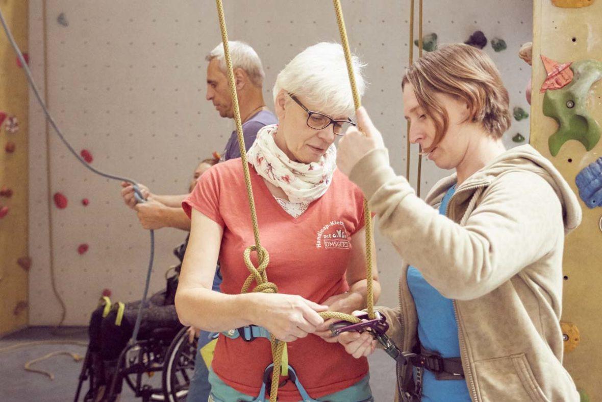 Helferin Anne zeigt einer Frau, wie sie sichert und Seil nachgibt.
