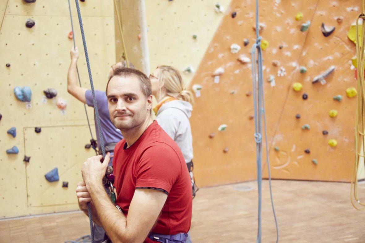 Helfer Steffen ist im Einsatz und hängt sich tief ins Seil, um einen Kletterer zu sichern.