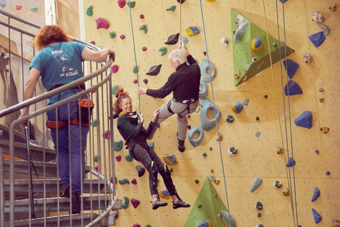 Petra und Volker hängen in den Seilen an der Kletterwand und lachen.