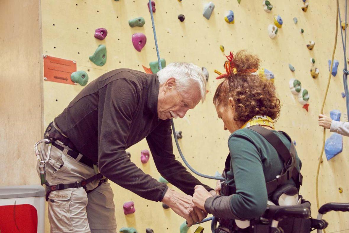 Volker hilft Petra, die im Rollstuhl stizt, die Sicherung anzubringen.
