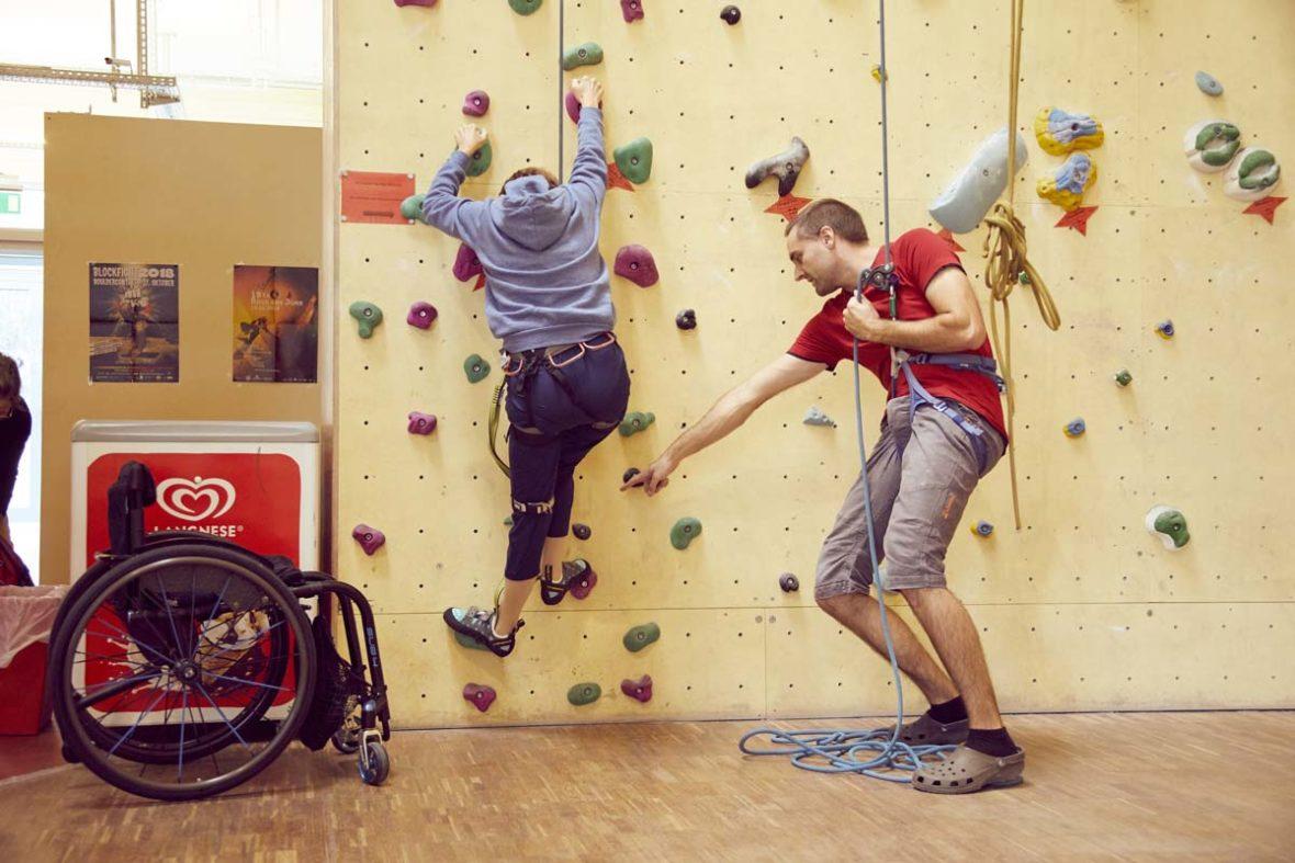 Steffen hilft einer Kletterin an der Wand dabei zu überlegen, wo sie ihren Fuß als nächstes hinsetzen kann.