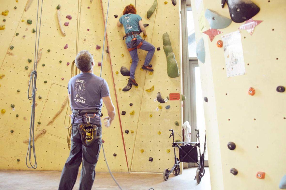 Sanna klettert an der Wand, rechts unter ihr auf dem Boden steht ihr Rollator. Ein Helfer sichert sie.