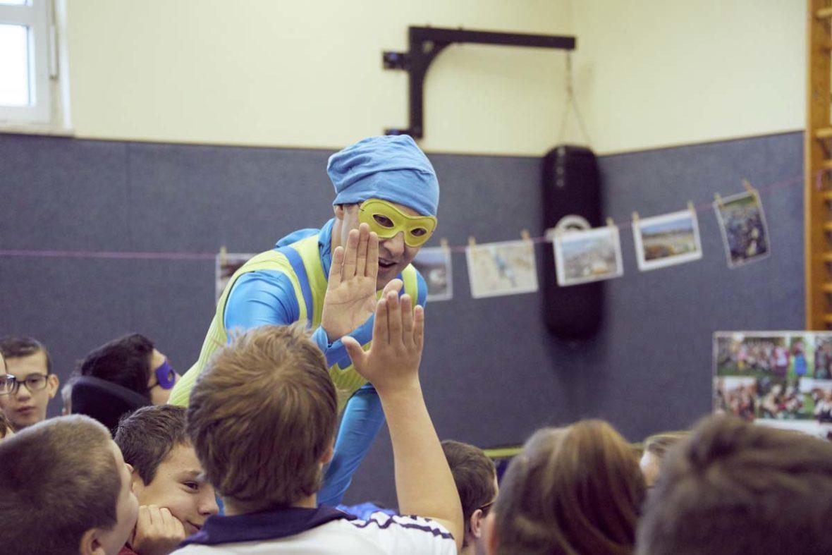 Der Stinknormale Superheld Kalle begrüßt einen Jungen mit einem Handschlag.