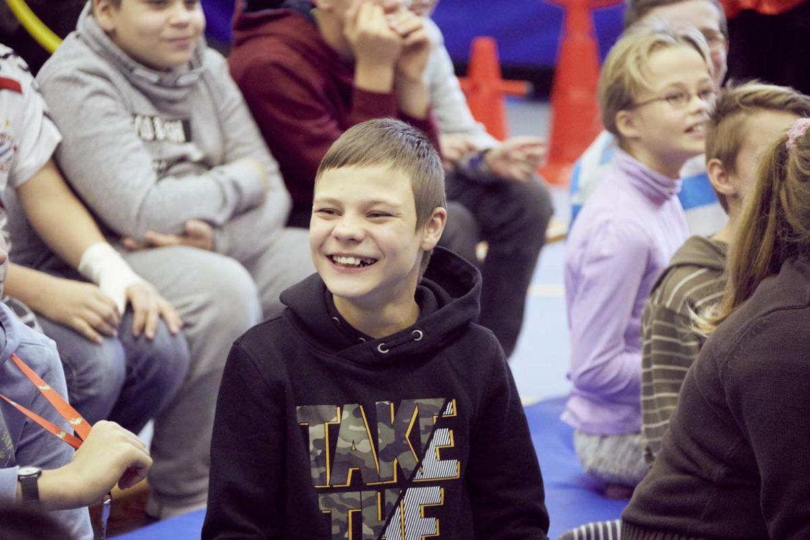Ein weiterer Junge der Förderschule Spektrum, der zwischen seinen Mitschülerinnen sitzt und lacht.