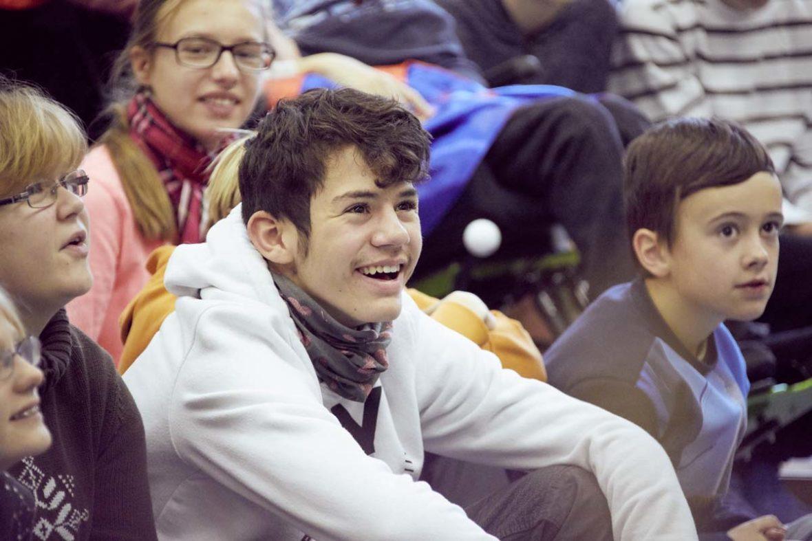 Ein Junge der Förderschule Spektrum, er sitzt mit anderen Kindern zusammen und lacht.