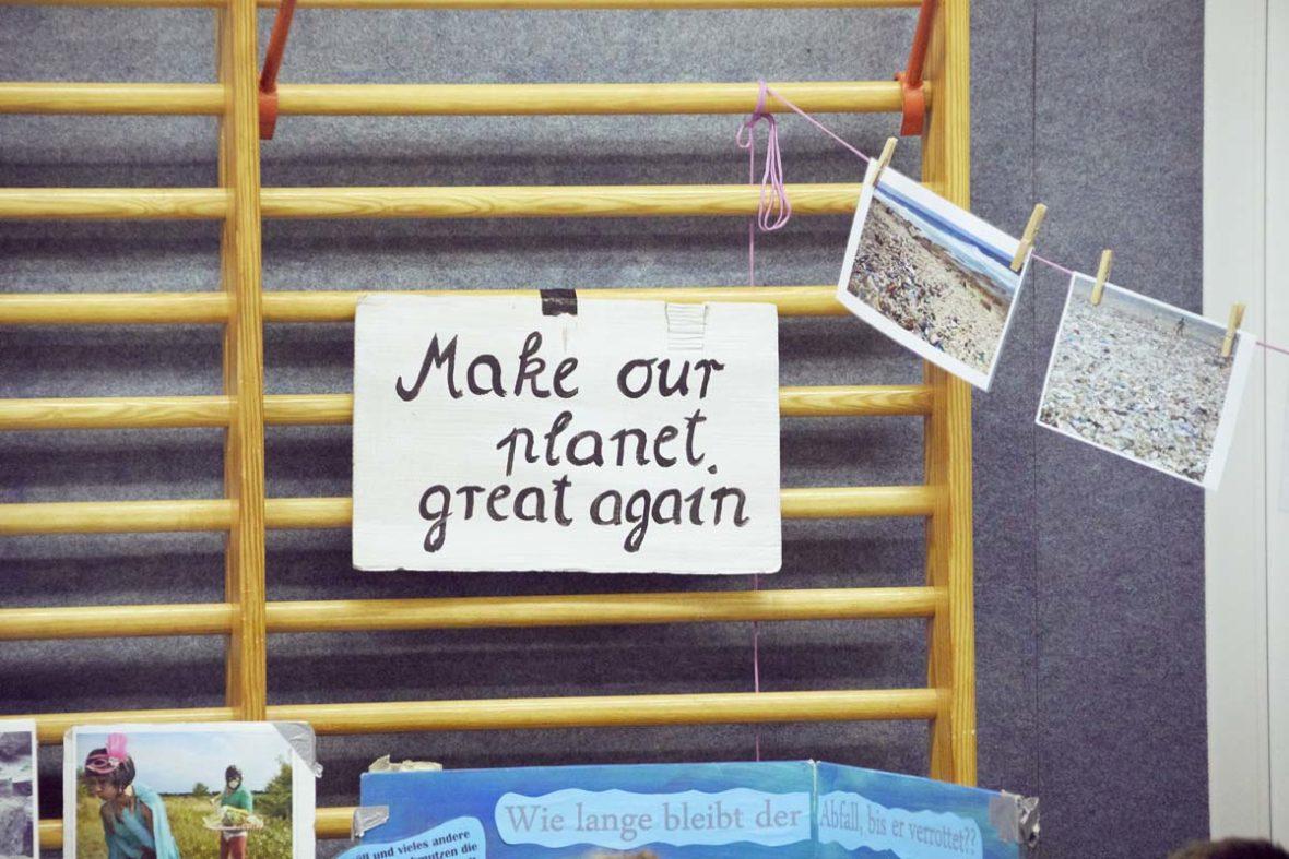 An der Kletterwand der Turnhalle hängt ein Schild mit dem Spruch: Make our planet great again.