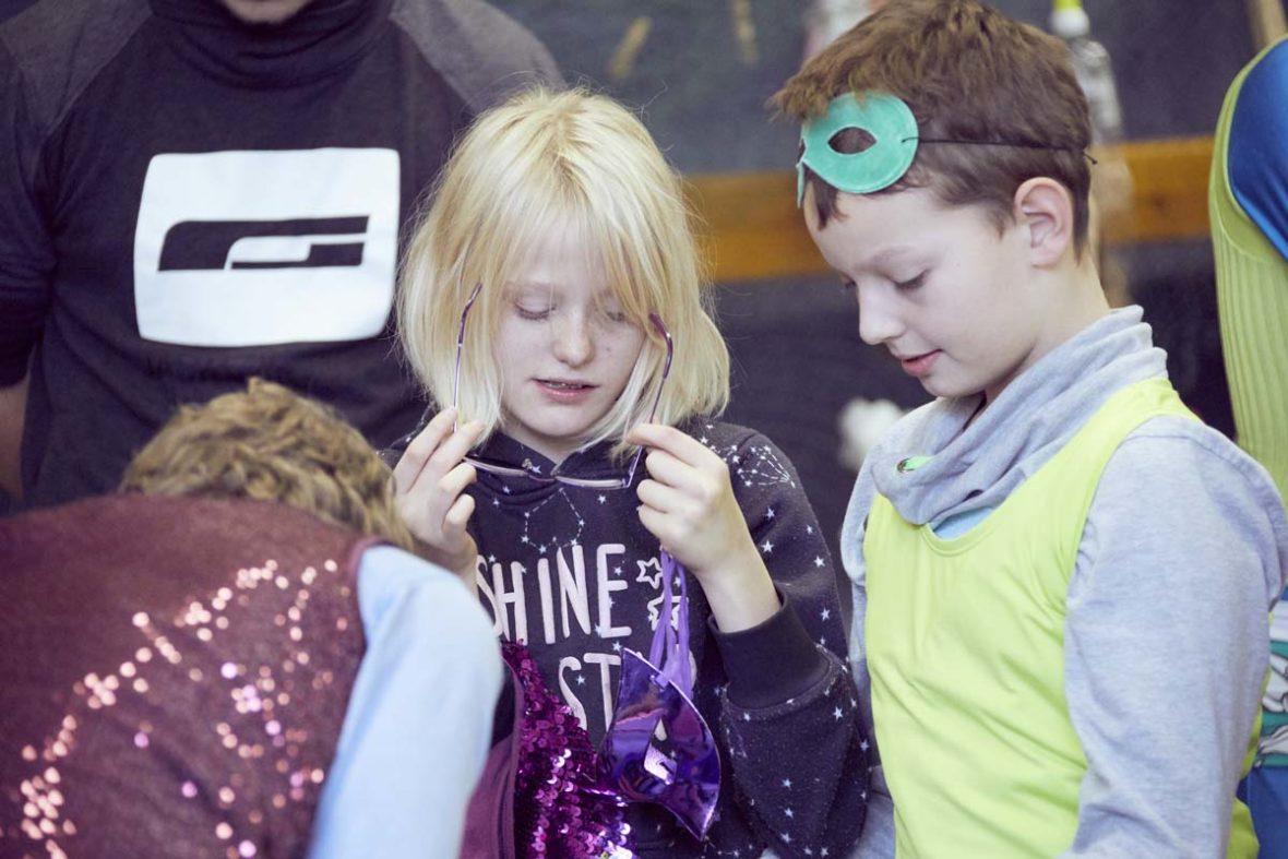 Ein Junge hat ein gelbes Top über seinen Pulli gezogen und trägt auf dem Kopf eine Maske.