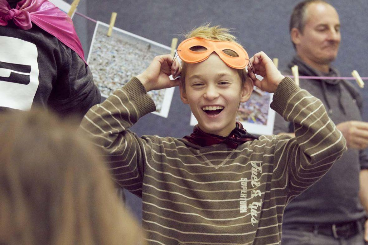 Ein lachender Junge mit Superheldenmaske.