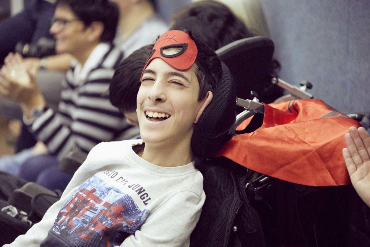 Ein Junge im Rollstuhl mit Superheldenmaske.