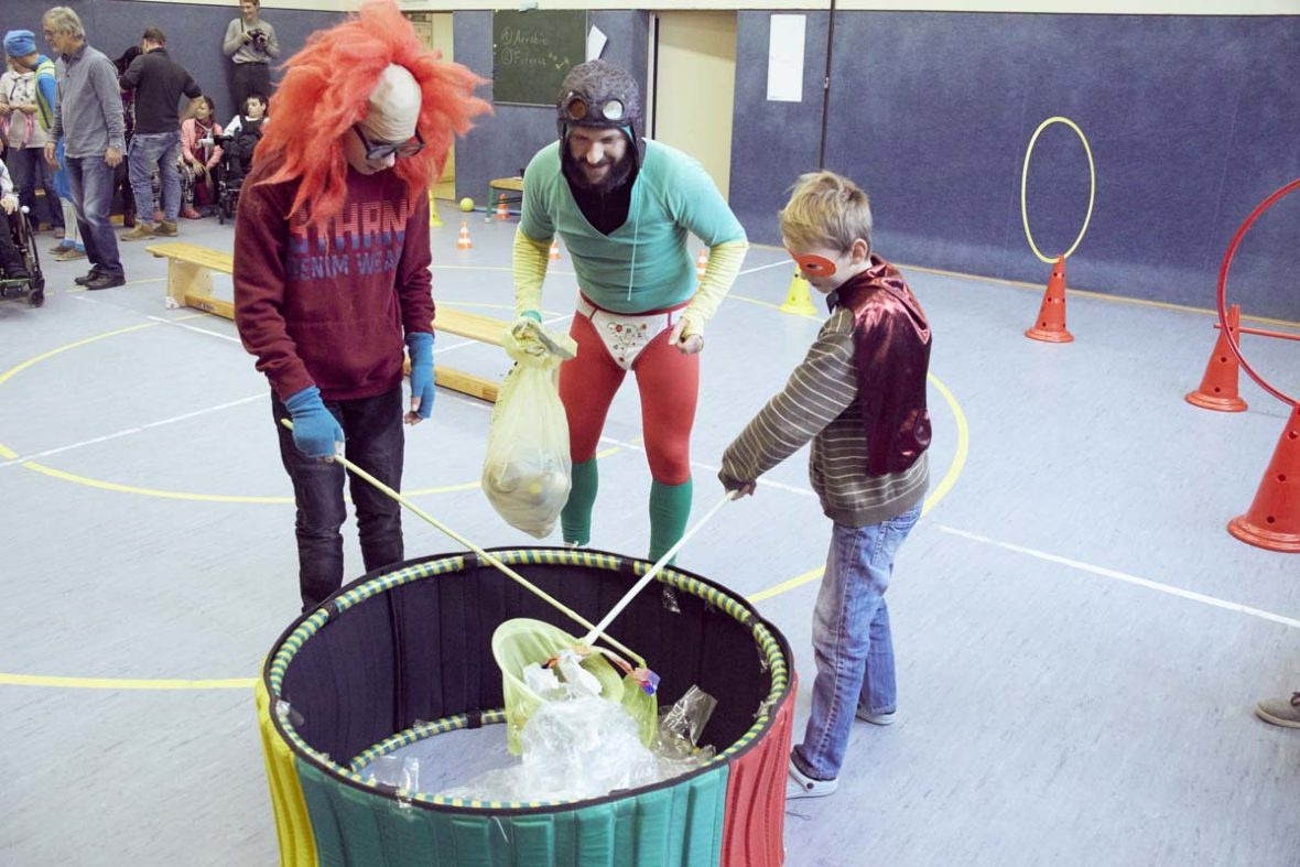 Zwei Kinder versuchen aus einem kleinen Becken, das mit Plastik gefüllt ist, Müll zu fischen.