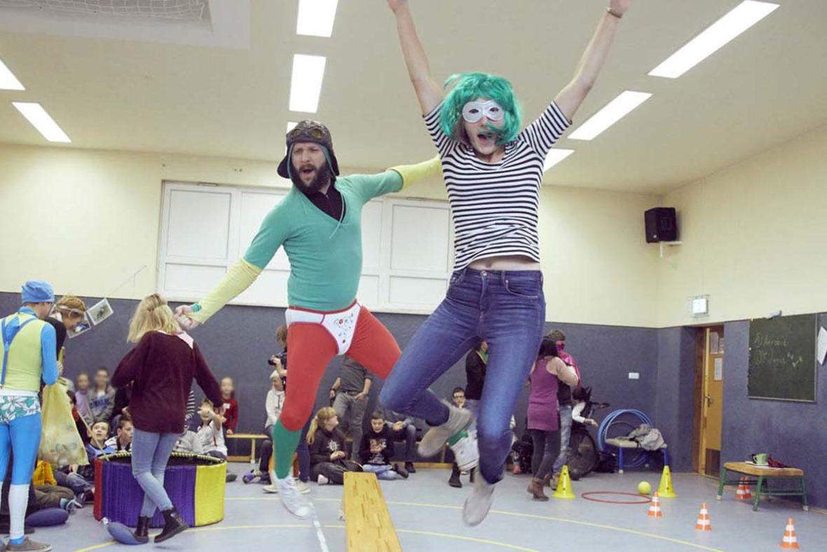Auch die Lehrer sind sich nicht zu schade, durch den Superheldenparcours zu gehen. Eine von ihnen springt von einer Bank, hinter ihr springt auch Katetschen Bernd.