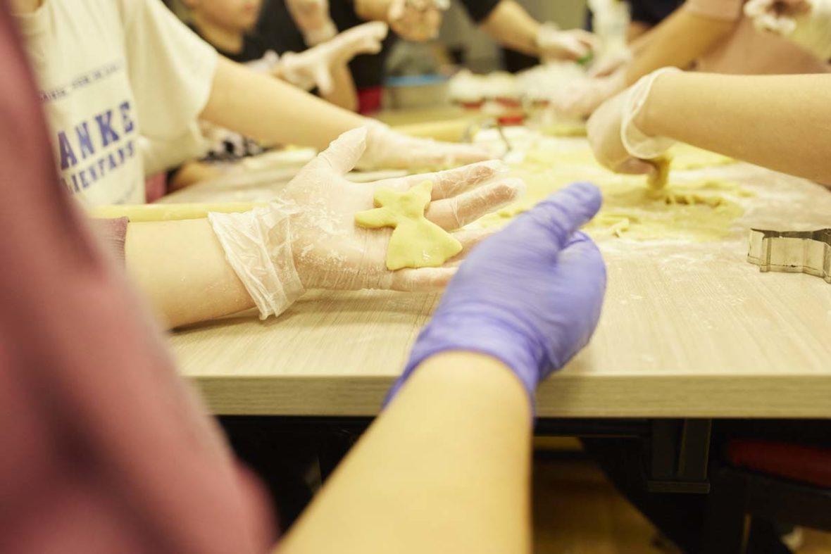 Viele Hände, im Vordergrund hält jemand einen Teigengel in der Hand.