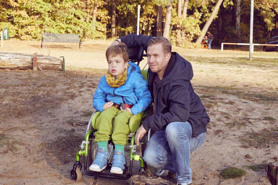 Daniel Burdach mit Sohn Filip, der Junge sitzt im Rollstuhl.