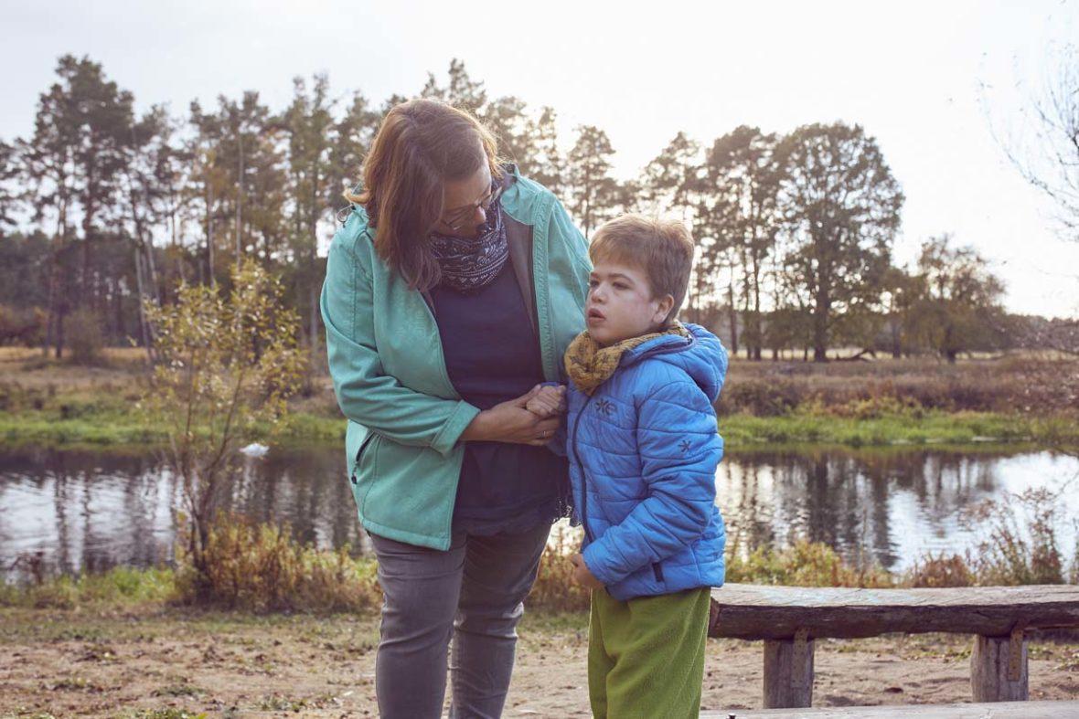 Nadine Burdach mit Filip am Flussufer. Der Junge sitzt nicht im Rollstuhl, sondern steht.
