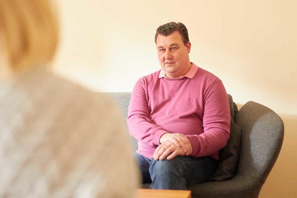 Michael Rieke sitzt auf einem grauen Sofa im Lotsenhaus. Er hat die Hände gefaltet auf sein linkes Bein gelegt.