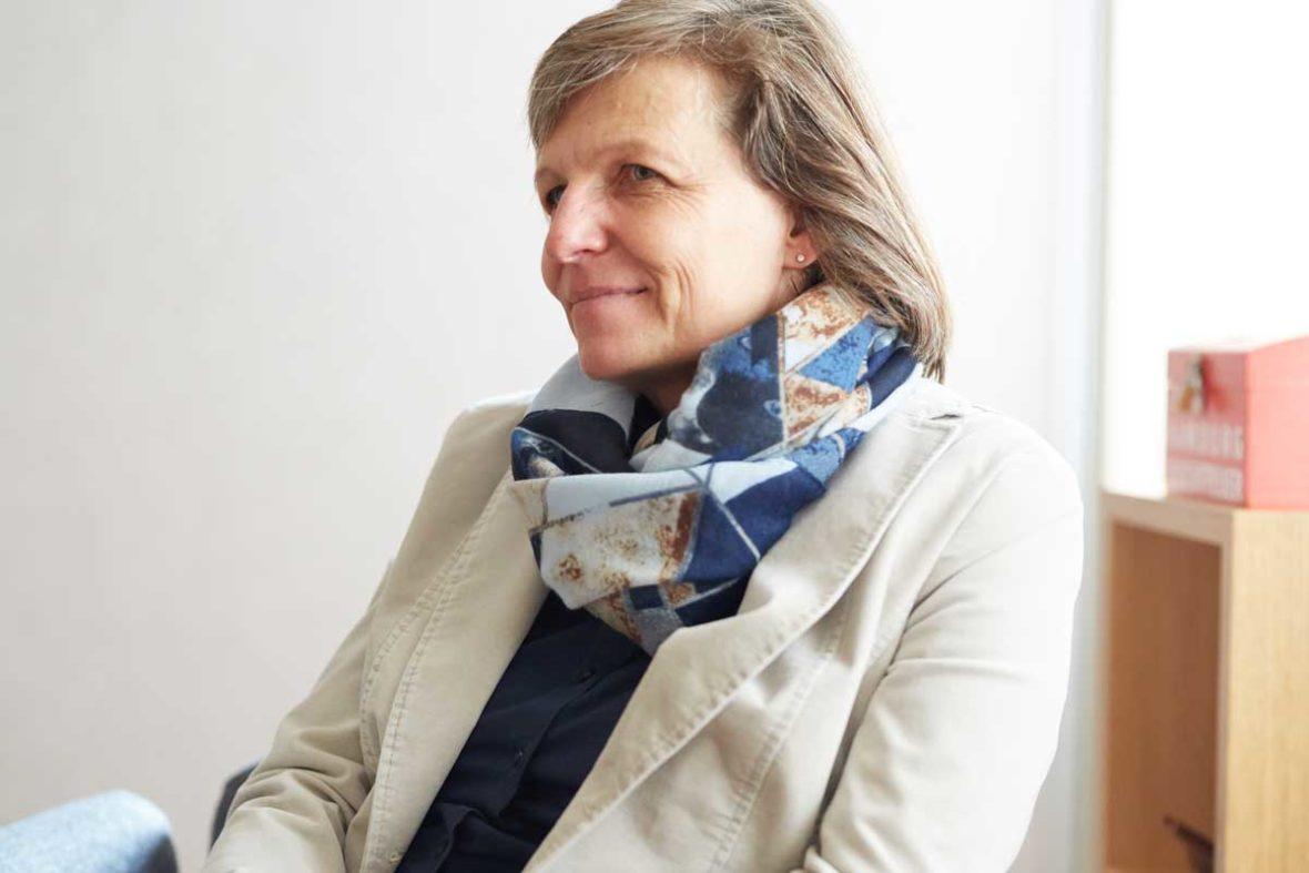 Bettina Kriegel sitzt auf einem Sessel im Lotsenhaus und schaut freundlich an der Kamera vorbei, in die Richtung, wo Michael Rieke sitzt. Sie trägt einen weißen Blazer und einen blaugemusterten Schal.