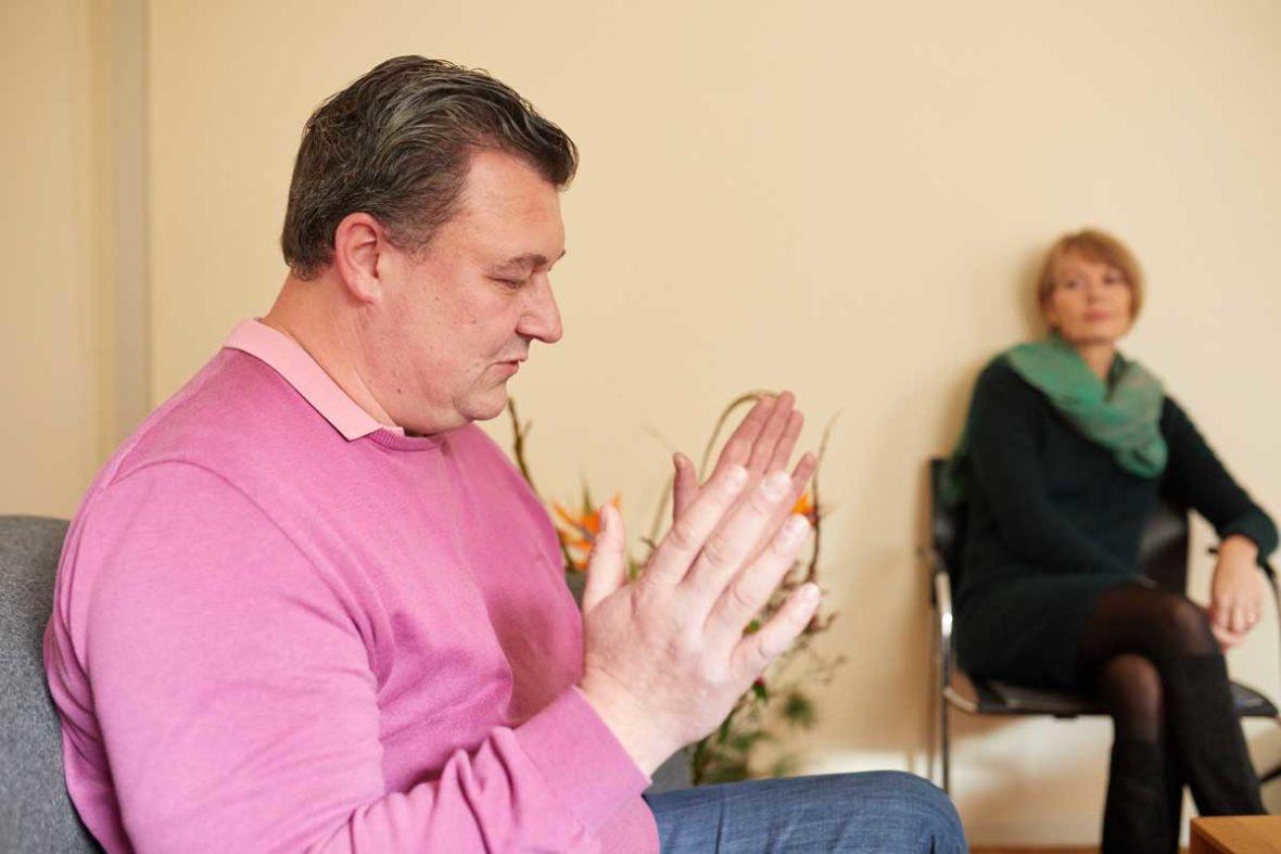 Michael Rieke erzählt gestikulierend von seinem Weg, die Trauer zu verarbeiten. Im Hintergrund sitzt Trauerberaterin Hannah Friedl und hört ihm aufmerksam zu.