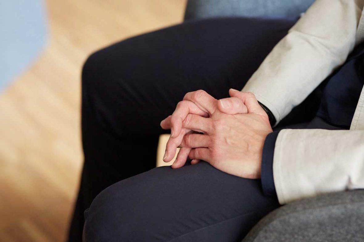 Man sieht Bettina Kriegels Hände, die im Schoß gefaltet sind.
