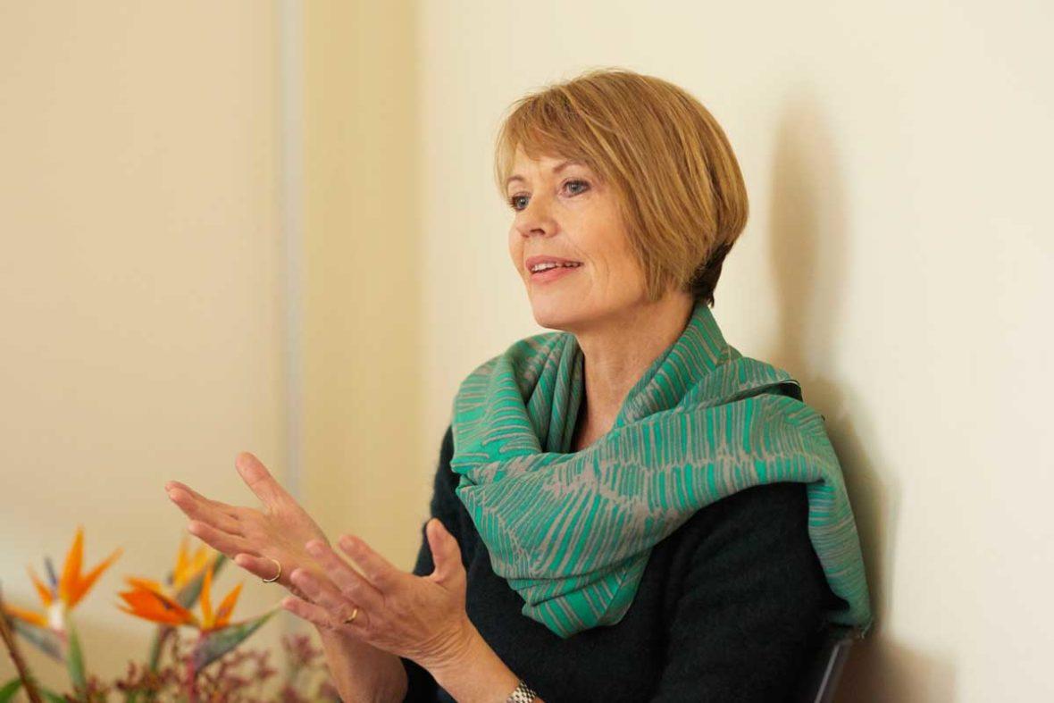 Trauerbegleiterin Hannah Friedl spricht über ihre Erfahrungen und hält dabei beide Hände mit den Handflächen nach oben vor sich. Sie trägt einen grünen Schal.
