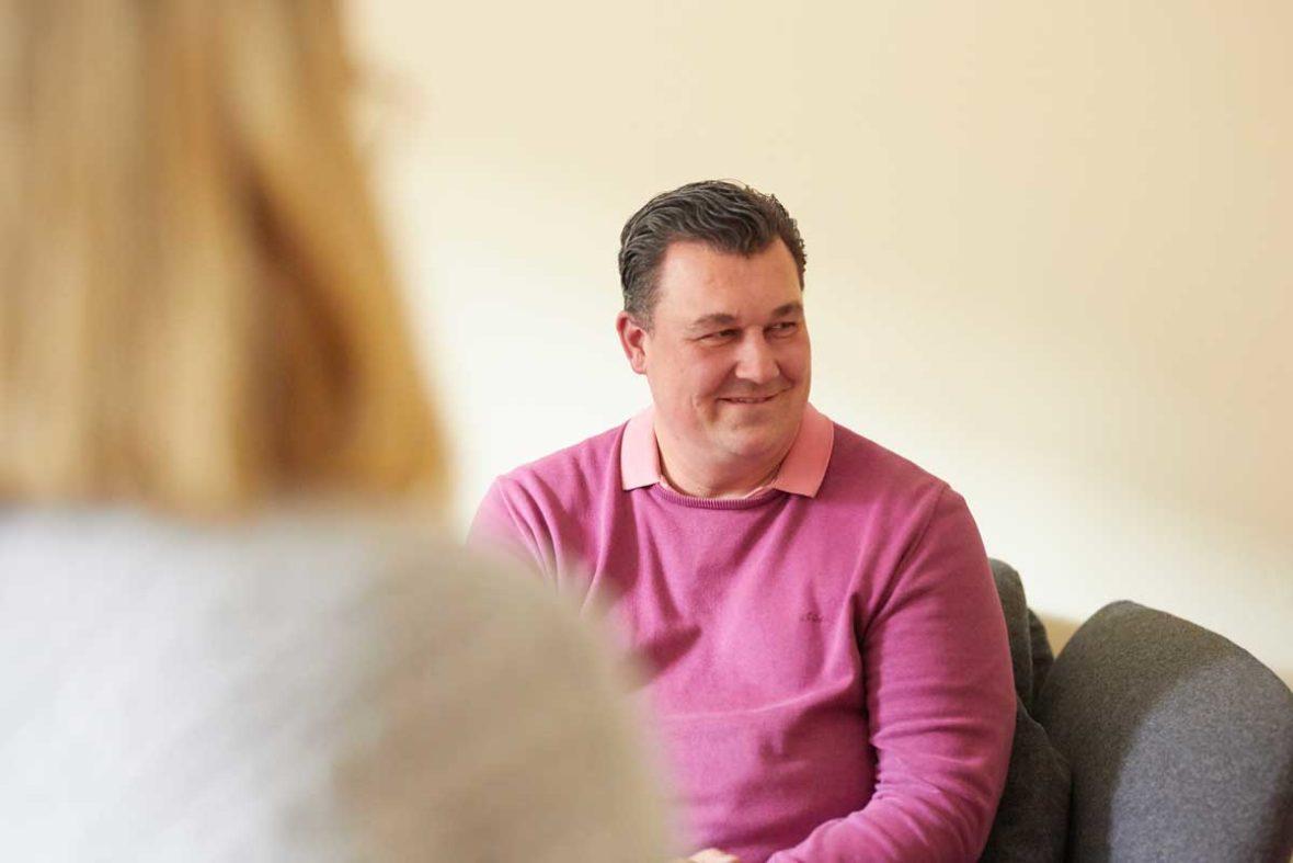 Michael Rieke lächelt in die Richtung, in der Trauerbegleiterin Hannah Friedl sitzt.
