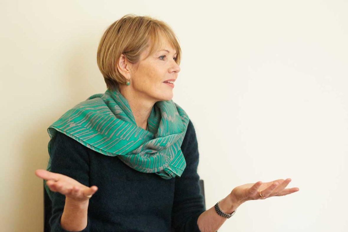 Hannah Friedl sitz vor der Wand und erzählt, dabei gestikuliert sie mit den Händen.
