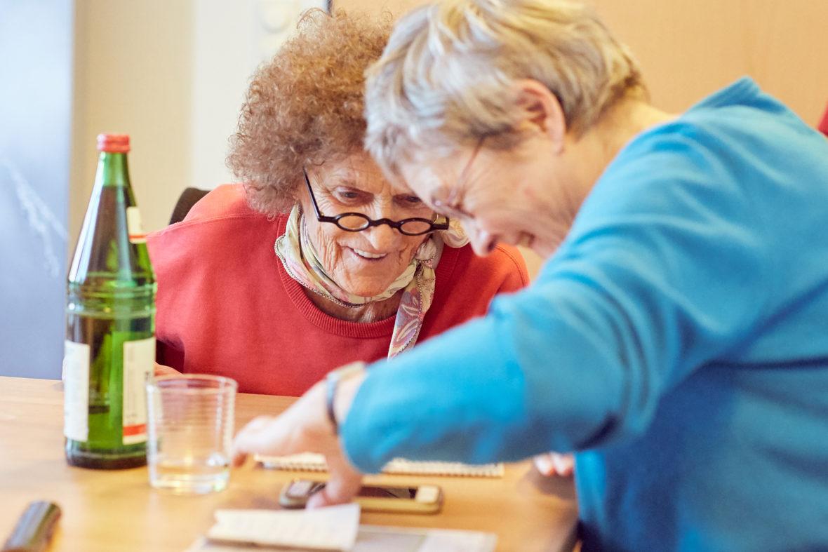 Zwei ältere Frauen beugen sich am Tisch lachend über ein Smartphone.