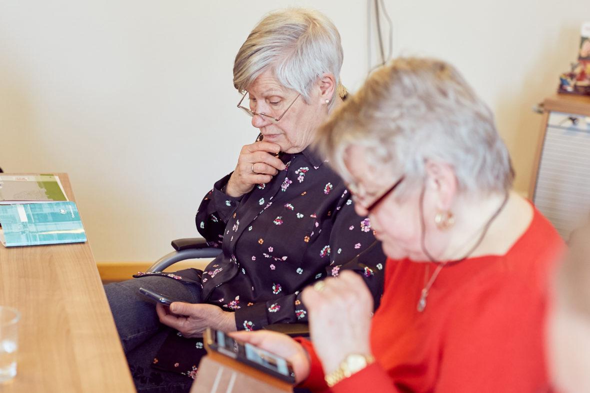 Zwei ältere Frauen sitzen am Tisch und schauen auf ihre Smartphones, die sie in der Hand halten.