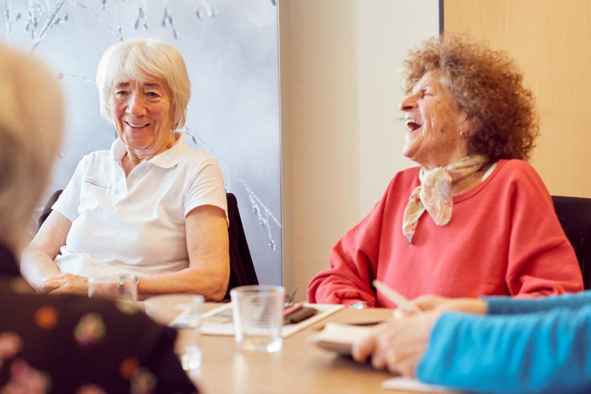 Zwei ältere Frauen sitzen am Tisch und lachen.