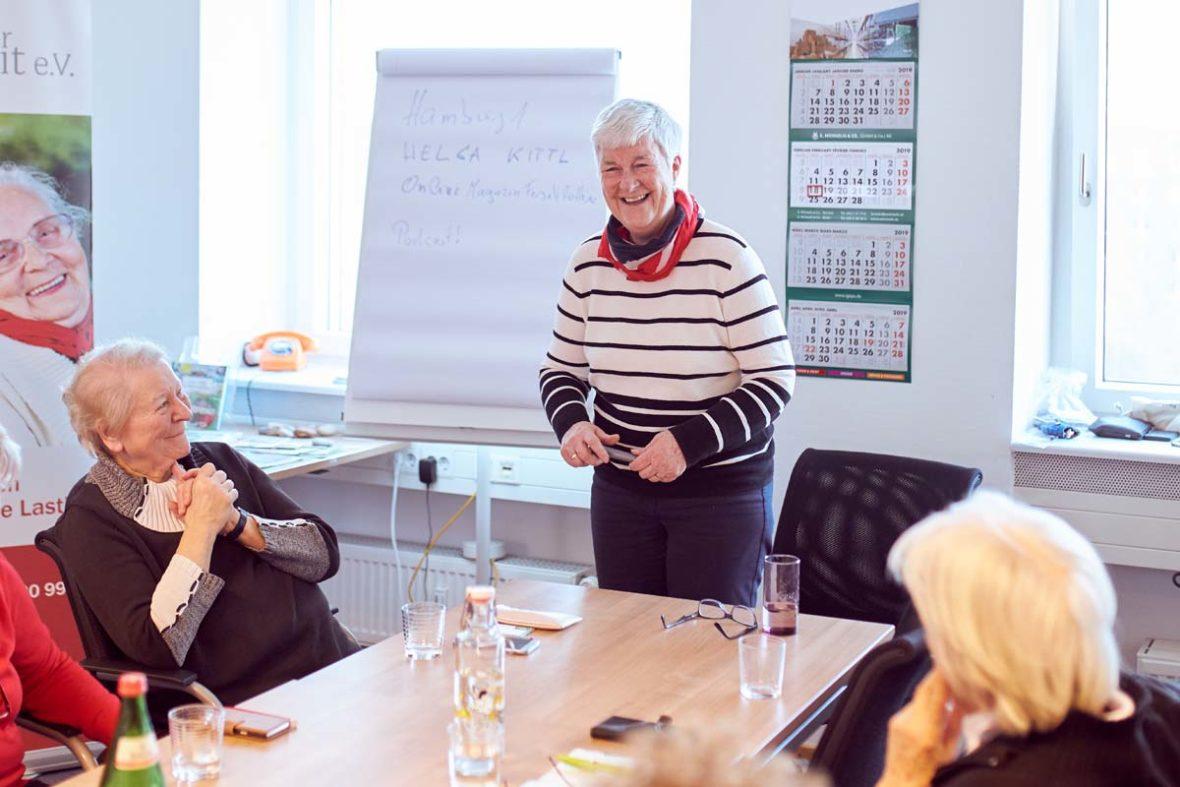 Dagmar Hirche steht vor einem Tisch, links und rechts sitzen zwei Frauen. Dagmar Hirche lächelt und hält etwas in der Hand. Hinter ihr ist ein Flipboard, auf das sie die Agenda des Kurses geschrieben hat.