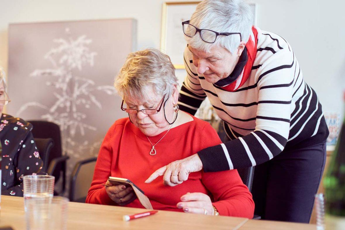 Dagmar Hirche steht hinter einer Teilnehmerin, die ihr Handy in der hand hält, und zeigt auf das Display.
